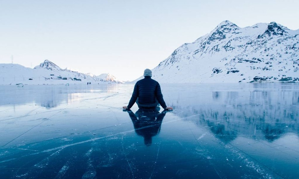 Man sitting on frozen lake